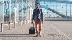 Jonge gebaarde mens in zonnebril die een zakenreis hebben, die de koffer trekken aan de luchthaven Actieve levensstijl, die hebbe stock video