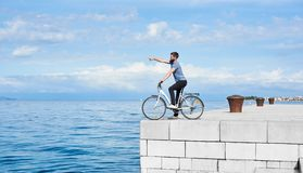 Jonge gebaarde mensentoerist die op fiets op hoog bedekte steenstoep van duidelijk blauw zeewater genieten stock fotografie