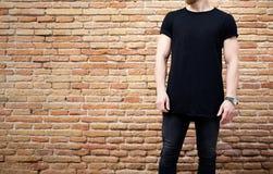 Jonge gebaarde spiermens zwarte t-shirt dragen en jeans die buiten stellen Lege bruine grungebakstenen muur op royalty-vrije stock afbeelding