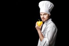 Jonge gebaarde witte eenvormig van In van de mensenchef-kok houdt gele groene paprika op zwarte achtergrond Stock Foto
