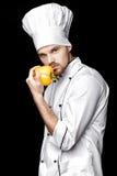 Jonge gebaarde witte eenvormig van In van de mensenchef-kok houdt gele groene paprika op zwarte achtergrond Stock Afbeeldingen