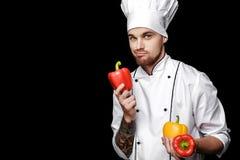 Jonge gebaarde witte eenvormig van In van de mensenchef-kok houdt groene paprika's op zwarte achtergrond Stock Foto