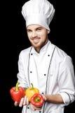 Jonge gebaarde witte eenvormig van In van de mensenchef-kok houdt groene paprika's op zwarte achtergrond Royalty-vrije Stock Foto