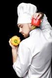 Jonge gebaarde witte eenvormig van In van de mensenchef-kok houdt groene paprika's op zwarte achtergrond Stock Fotografie
