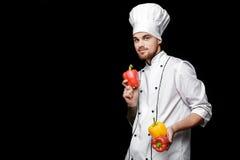 Jonge gebaarde witte eenvormig van In van de mensenchef-kok houdt groene paprika's op zwarte achtergrond Stock Foto's