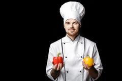 Jonge gebaarde witte eenvormig van In van de mensenchef-kok houdt groene paprika's op zwarte achtergrond Royalty-vrije Stock Foto's
