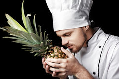 Jonge gebaarde witte eenvormig van In van de mensenchef-kok houdt Verse ananas op zwarte achtergrond Stock Afbeeldingen
