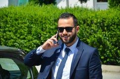 Jonge gebaarde zakenman in elegant kostuum met telefoon Stock Fotografie