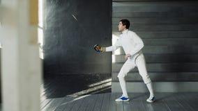 Jonge geconcentreerde de praktijk van de schermermens het schermen oefeningen en binnen opleiding voor de Olympische spelenconcur Royalty-vrije Stock Foto's