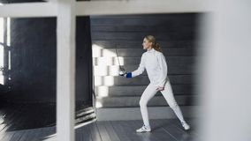 Jonge geconcentreerde de praktijk van de schermervrouw het schermen oefeningen en binnen opleiding voor de Olympische spelenconcu Stock Foto