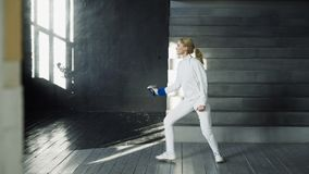 Jonge geconcentreerde de praktijk van de schermervrouw het schermen oefeningen en binnen opleiding voor de Olympische spelenconcu Stock Afbeeldingen