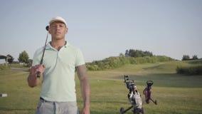 Jonge geconcentreerde mens die van het Middenoosten weg met de golfclub op zijn schouder kijken Knap mensen speelgolf op stock video