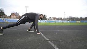 Jonge geconcentreerde mens op een renbaan die bij stadion voorbereidingen treffen te lopen stock video