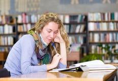 Jonge geconcentreerde student die een tabletcomputer in een bibliotheek met behulp van Stock Foto