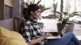 Jonge geconcentreerde vrouw, die in de ruimte of de werkruimte met vensters zitten Het werken aan laptop op haar benen en hoofdte stock video