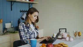 Jonge geconcentreerde vrouw die in keuken werken die laptop computer met behulp van tijdens ontbijt in de ochtend stock footage