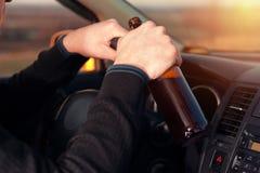 Jonge gedronken mens die een auto drijven en bier drinken stock afbeeldingen