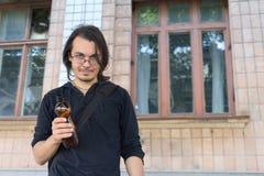 Jonge gedronken mens die plastic fles houdt royalty-vrije stock foto's
