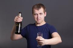 Jonge gedronken mens met fles champagne en glas stock foto