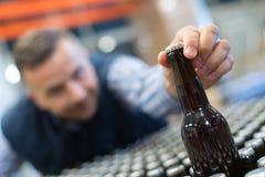 Jonge gedronken zakenman die flessenbier bereiken stock afbeelding