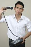 Jonge gefrustreerde mens die telefoon in woede werpt stock fotografie