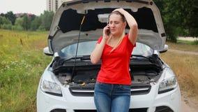 Jonge gefrustreerde vrouw die op de gebroken auto leunen en de dienst voor hulp roepen stock video