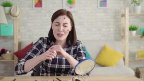 Jonge gefrustreerde vrouw met mollen op haar gezicht die in de spiegel kijken en make-up doen stock videobeelden