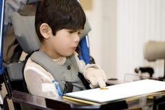 Jonge gehandicapte jongen die in rolstoel bestudeert Royalty-vrije Stock Afbeeldingen