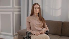 Jonge gehandicapte vrouw het luisteren muziek thuis stock footage