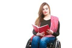 Jonge gehandicapte vrouw in rolstoel met boek Royalty-vrije Stock Afbeelding