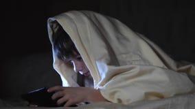 Jonge geitjes één gebruikend tabletpc onder deken bij nacht De de computerspelen van jongensspelen stock footage