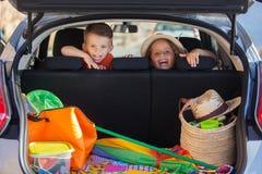 Jonge geitjes in auto die bij de zomervakantie aankomen stock fotografie