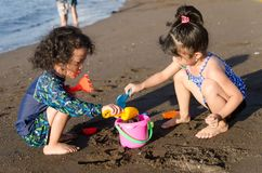 Jonge geitjes bij strand het spelen met het zand stock afbeelding