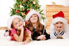 Jonge geitjes in de hoeden van de Kerstman Stock Afbeeldingen