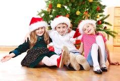 Jonge geitjes in de hoeden van de Kerstman het omhelzen Stock Foto's