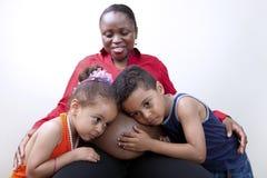 Jonge geitjes die aan mamma`s zwangere buik luisteren Stock Afbeeldingen