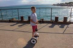 Jonge geitjes die autoped in de zomer berijden dichtbij het overzees Saldoraad voor kinderen Nieuwe moderne technologieën van eco Stock Afbeeldingen