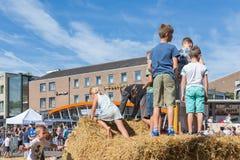 Jonge geitjes die bij hooibalen spelen op een Nederlands landbouwaardappelfestival Stock Foto's