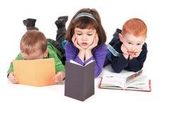 Jonge geitjes die boeken lezen Stock Afbeeldingen