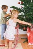 Jonge geitjes die de Kerstmisboom verfraaien Stock Foto's