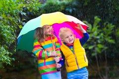Jonge geitjes die in de regen onder kleurrijke paraplu spelen Stock Afbeeldingen