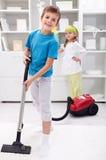 Jonge geitjes die de ruimte schoonmaken die - een stofzuiger met behulp van Royalty-vrije Stock Foto