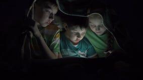 Jonge geitjes die in de tablet onder de dekking spelen stock footage