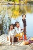 Jonge geitjes die dichtbij het meer in de herfst spelen Stock Foto's