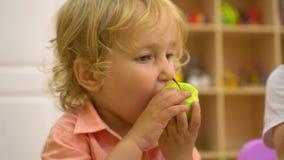 Jonge geitjes die een appel in peuterlunch in kleuterschool eten stock footage