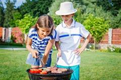 Jonge geitjes die een barbecuepartij hebben Stock Foto's