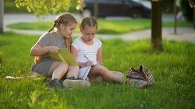 Jonge geitjes die een boek in de zomertuin lezen Peuter en vrienden die spelen leren Meisjes die hun thuiswerk doen stock footage