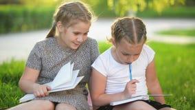 Jonge geitjes die een boek in de zomertuin lezen Peuter en vrienden die spelen leren Meisjes die hun thuiswerk doen stock videobeelden