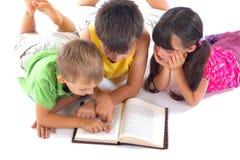 Jonge geitjes die een boek lezen Stock Afbeelding