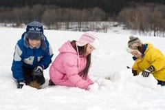 Jonge geitjes die een Fort van de Sneeuw bouwen Stock Afbeelding